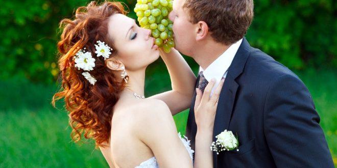 Bräutigam wird von Braut mit Trauben gefüttert